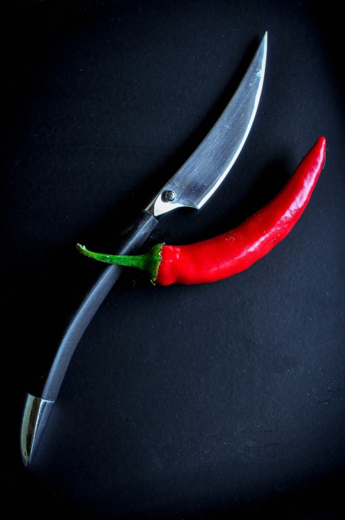 Chilli and knife on black